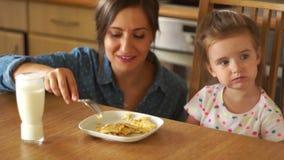 Den härliga brunetten matar hennes dotter Flickan öppnar hennes munsned boll Moderskratt Förvanskade ägg och mjölkar lager videofilmer