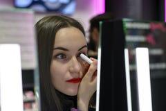 Den härliga brunetten med röd läppstift testar ögonskuggorna i skönhetlager Royaltyfri Fotografi