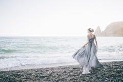 Den härliga brunettflickan i lång grå spolning i vindklänningen göras av tyllhåll med en hand som klänningblickarna profilerar royaltyfria bilder