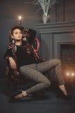 Den härliga brunettflickan i mode beklär sammanträde som poserar på den chear near spisen för gammal tappning härlig för studiokv Royaltyfri Bild