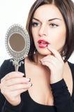 Den härliga brunettflickan ser i spegel Arkivfoton