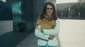 Den härliga brunettkvinnan med böcker i händer går i gatan och ler lager videofilmer