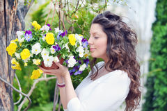 Den härliga brunettkvinnan som luktar en vår, blommar Arkivfoton