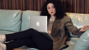 Den härliga brunettmodellen, med lockigt hår, sitter med en bärbar dator på soffan stock video
