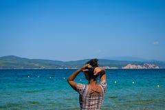 Den härliga brunettmodellen poserar på en strand Royaltyfria Bilder