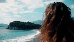 Den härliga brunnetekvinnan i röd bikini solbadar på stranden lager videofilmer