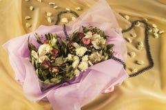 den härliga buketten av blommor, svart pryder med pärlor på guld- organza Arkivbilder