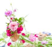 Den härliga buketten av rosa färger blommar peons, blåklinter och röda rosor på vit bakgrund med utrymme för text arkivbild