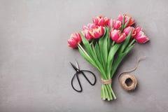 Den härliga buketten av rosa tulpanblommor för våren på bästa sikt för stentabell i lägenhet lägger stil royaltyfri bild