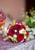 Den härliga buketten av steg blommor på tabellen. Bröllopbukett av röda rosor. Elegant bröllopbukett på tabellen på restaurangen Arkivbild