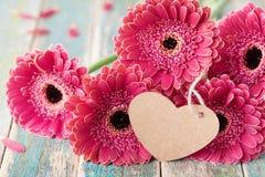 Den härliga buketten från gerberatusensköna blommar med hälsninganmärkningen i form av hjärta för valentin, kvinna eller mors dag Royaltyfria Bilder