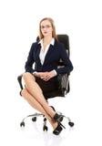 Den härliga caucasian affärskvinnan sitter på en stol med honom arkivfoton