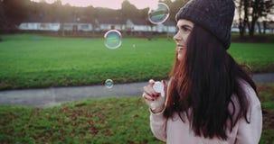 Den härliga Caucasian flickan med långt lockigt hår blåser bubblor i eftermiddagen stock video