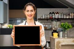 Den härliga Caucasian kvinnan i baristaförklädet som rymmer det tomma svart tavlatecknet inom coffee shop - ordna till för att sä Royaltyfria Foton