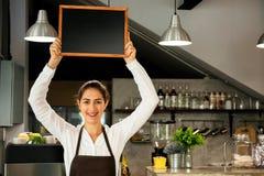 Den härliga Caucasian kvinnan i baristaförklädet som rymmer det tomma svart tavlatecknet inom coffee shop - ordna till för att sä Royaltyfri Bild