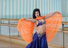 Den härliga caucasian kvinnan i dräkten för magdans dansar inomhus på konditiongrupp arkivbild