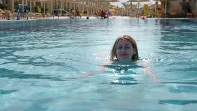 Den härliga Caucasian modellen, den unga kvinnan simmar i en pöl med blått vatten i ett hotell, under den öppna himlen mot som kr lager videofilmer