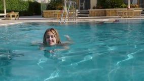 Den härliga Caucasian modellen, den unga kvinnan simmar i en pöl med blått vatten i ett hotell, under den öppna himlen mot som kr stock video