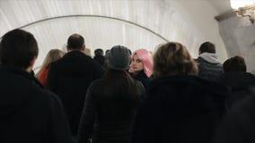 Den härliga caucasian unga flickan med rosa hår går till och med en folkmassa av folk i tunnelbana Kvinnan med rosa hår vänder ti arkivfilmer