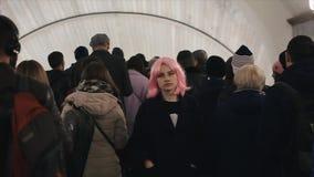 Den härliga caucasian unga flickan med rosa hår går till och med en folkmassa av folk Nätt kvinna med rosa hår i gångtunnel lager videofilmer
