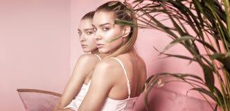 Den härliga caucasianen kopplar samman kvinnliga modeller på rosa bakgrund Arkivbilder