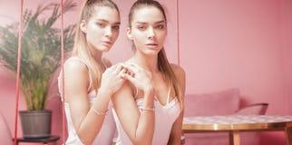 Den härliga caucasianen kopplar samman kvinnliga modeller på rosa bakgrund Royaltyfria Foton