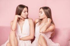 Den härliga caucasianen kopplar samman kvinnliga modeller på rosa bakgrund Royaltyfri Fotografi