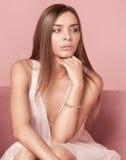 Den härliga caucasianen kopplar samman kvinnliga modeller på rosa bakgrund Royaltyfri Foto