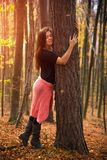 Den härliga charmiga flickan kramar en trädstam i höstskogen royaltyfri fotografi