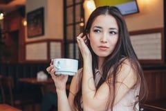 Den härliga charmiga romantiska brunetten som ler den asiatiska flickan, har frukosten med kaffe på kafét arkivfoton