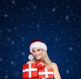Den härliga damen i jullock rymmer en uppsättning av gåvor arkivfoto