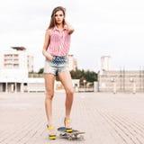 Den härliga damen i korta jeanskortslutningar står på skateboarden Royaltyfri Fotografi