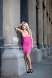 Den härliga damen lutar mot kolonner i en klänning Fotografering för Bildbyråer