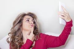 Den härliga damen med den röda klänningen tar en selfie Arkivbild