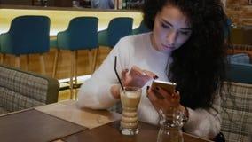 Den härliga damen med lockigt hår i en restaurang arbetar på telefonen och att drömma arkivfilmer