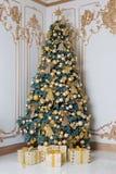 Den härliga dekorerade guld- julgranen med gåva boxas i lyxig klassisk inre royaltyfri bild