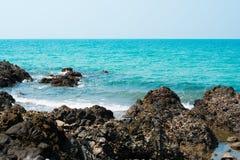 Den härliga djupblå stranden och stranden vaggar Arkivbild