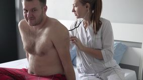 Den härliga doktorn sätter på en stetoskop och lyssnar till patientens andedräkt i avvärjer arkivfilmer