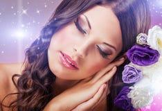 Den härliga drömlika kvinnan med ögon stängde sig, bredvid purpurfärgade blommor Royaltyfri Fotografi