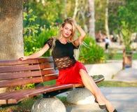 Den härliga drömlika kvinnan på bänk i stad parkerar i sommar fotografering för bildbyråer