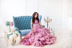 Den härliga eleganta gravida kvinnan med romantiska rosa färger klär, frisyren och sminket Studioinreskott Royaltyfri Bild