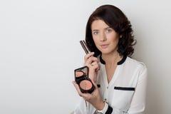 Den härliga eleganta kvinnan med smink visar de dekorativa kosmetiska produkterna i krus för att applicera makeup på en vit backg Fotografering för Bildbyråer