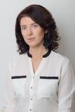 Den härliga eleganta kvinnan visar applikationen av makeup på en vit bakgrund i studio Royaltyfri Fotografi