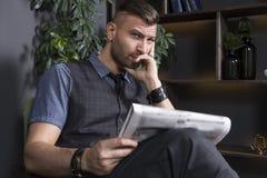 Den härliga eleganta stilfulla mannen sitter i en fåtölj med en tidning i en lyxig inre Den allvarliga unga affärsmannen läser ny royaltyfri bild