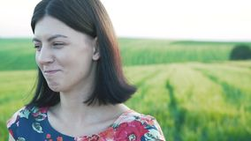 Den härliga europeiska flickan med kort svart hår i kort kjol med blommor ser kameran, startar att skratta arkivfilmer