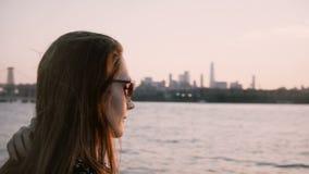 Den härliga europeiska flickan med långt hår som blåser i vinden, står av vattnet som ser den New York City solnedgången 4K lager videofilmer
