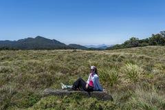 Den härliga europeiska kvinnan som sitter på, vaggar på nationalparken royaltyfria bilder