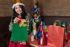 Den härliga för klänningen och Santa Claus för kvinnakläder röda gåvan för gräsplan för visningen för hatten hänger löst föreståe fotografering för bildbyråer