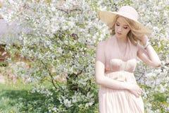 Den härliga försiktiga älskvärda flickan i en sommarhatt med ett ljust smink, med fulla kanter går i blommande trädgård på en lju Royaltyfria Bilder