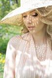 Den härliga försiktiga älskvärda flickan i en sommarhatt med ett ljust smink, med fulla kanter går i blommande trädgård på en lju Arkivbild